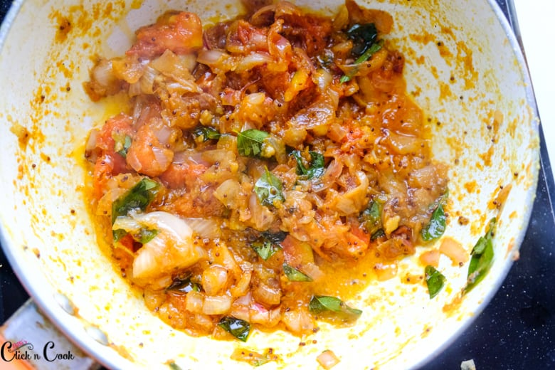 onion and tomato gravy is being cooked in saute pan