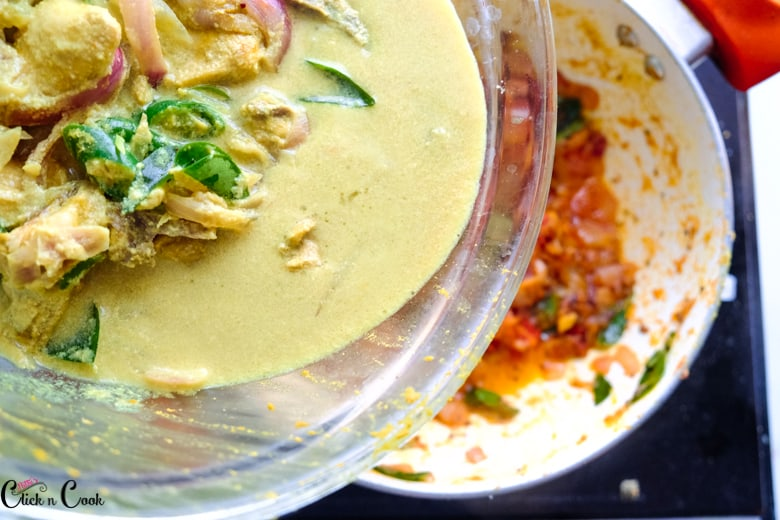chicken gravy in glass bowl is being added to onion tomato gravy in saute pan