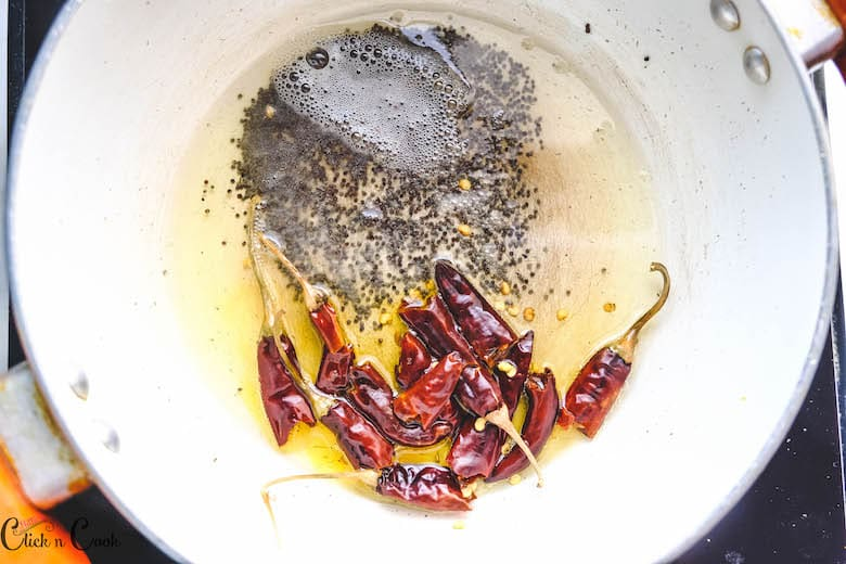 mustard and dry redchillies are being sauted in white fry pan