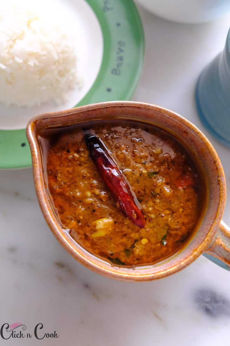 Garlic curry / poondu kuzhambu with red chilli on top served in small ceramic sauce bowl with rice aside.