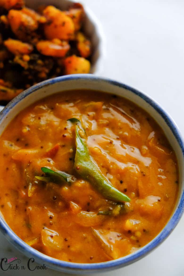 Tomato kurma served in glass bowl, seasoned with mustard seeds and green chilli.