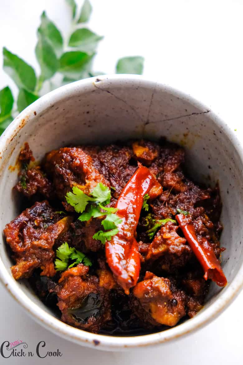 close up shot of spicy mutton chops served in bowl with curryleaves aside