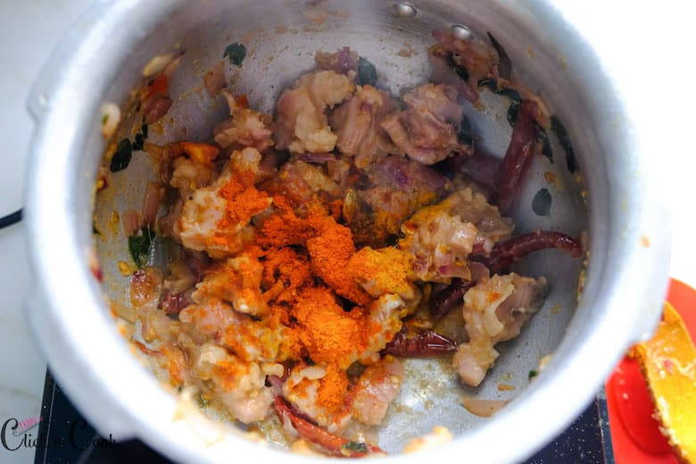 chili powder and turmeric powders are added to mutton pieces cooked in deep pot