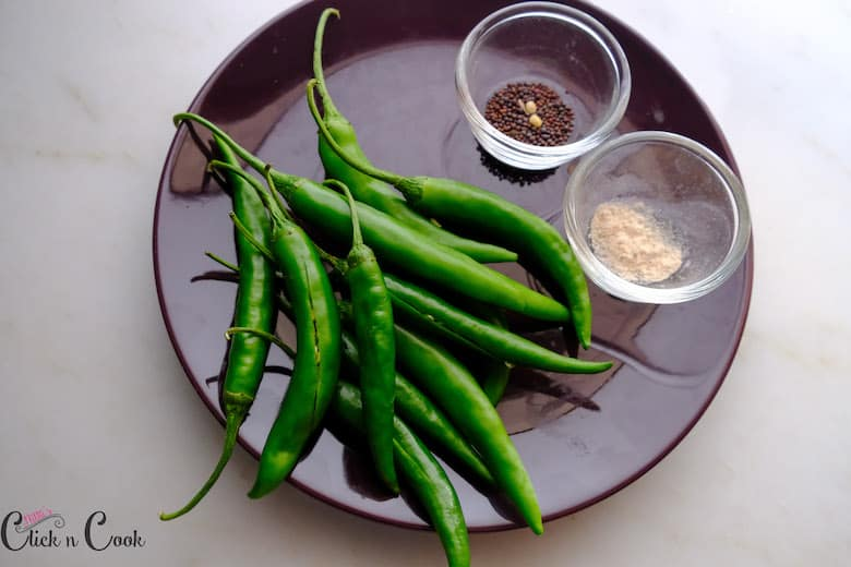 slited greenchillies are in plate and mustard seeds and asafoetida are in small glass bowl
