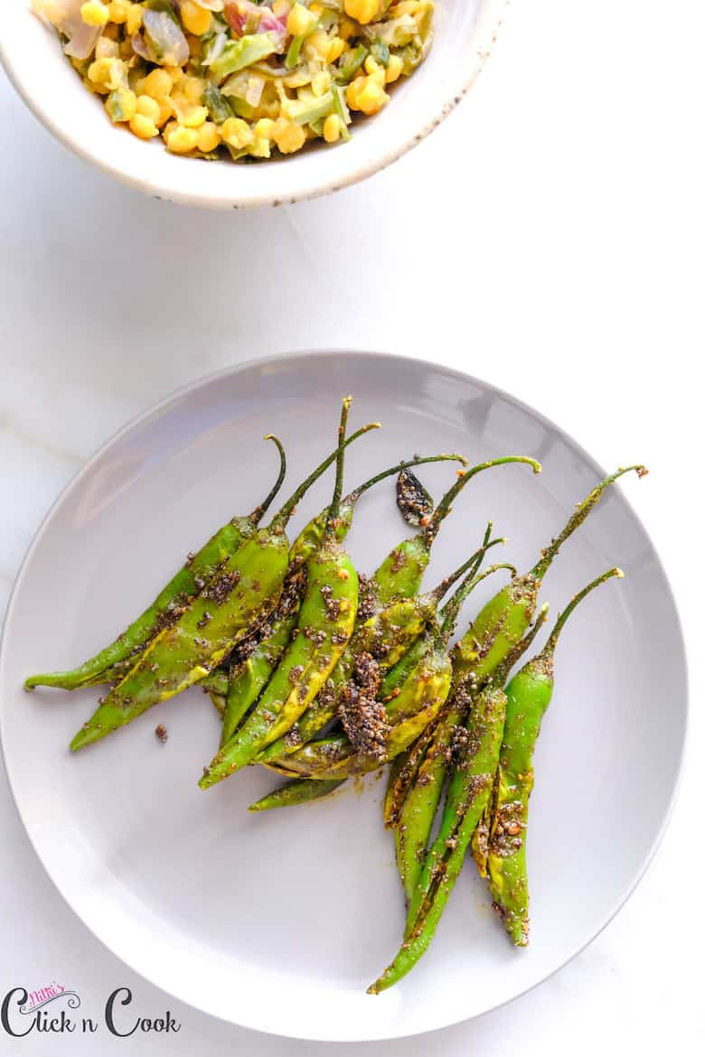 Mirchi Masala served in small plate with bowl of kootu aside