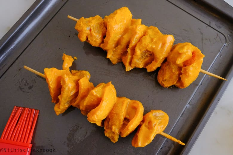 Chicken tikka is skewred and placed on the baking tray