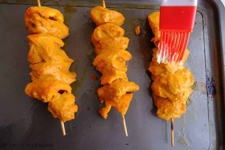 Butter is being basted over the skewered chicken tikka in baking tray