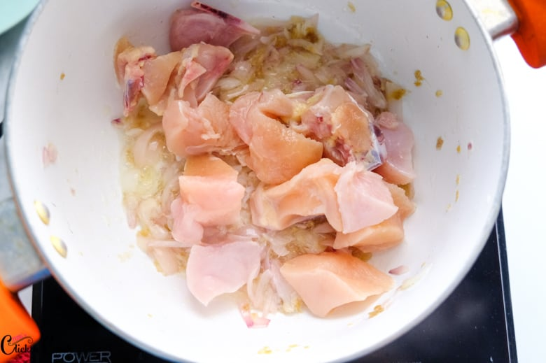 chicken and onion is being cooked in saute pan