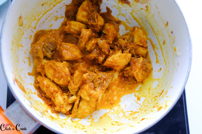 chicken is being cooked with spices in saute pan