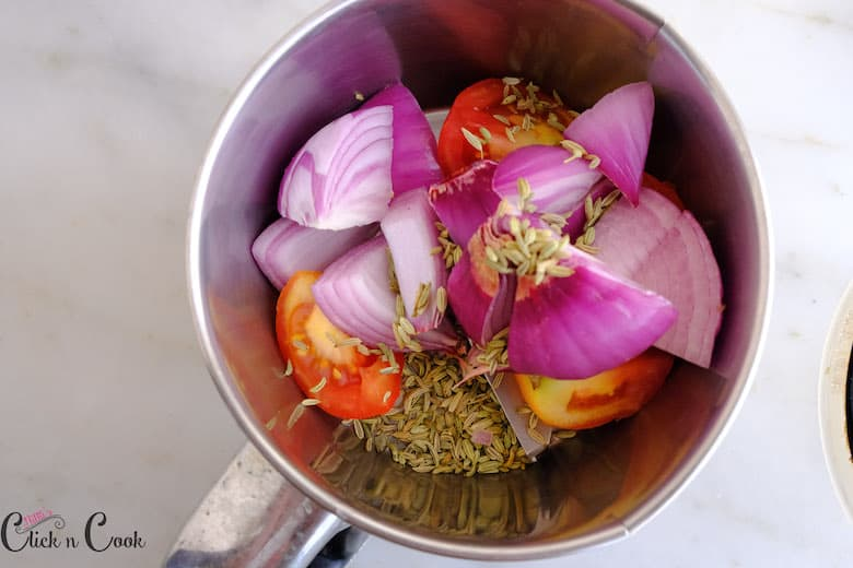 Onions, tomato and fennel seeds are in blender jar
