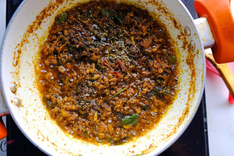 pepper and fennel powder is sprinkled over the cooked mutton in saute pan