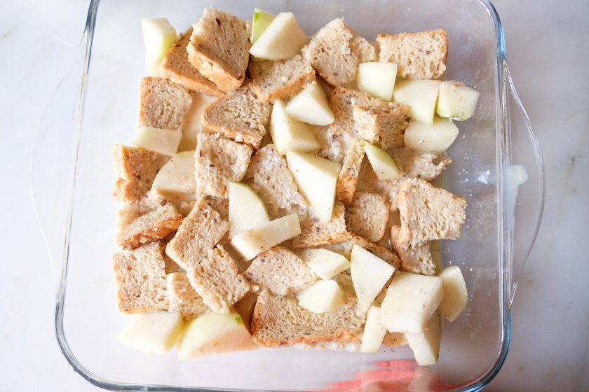 The milk mixture is being added to the bread cubes and pears in the baking tray. Allowing the bread to absorb the milk.