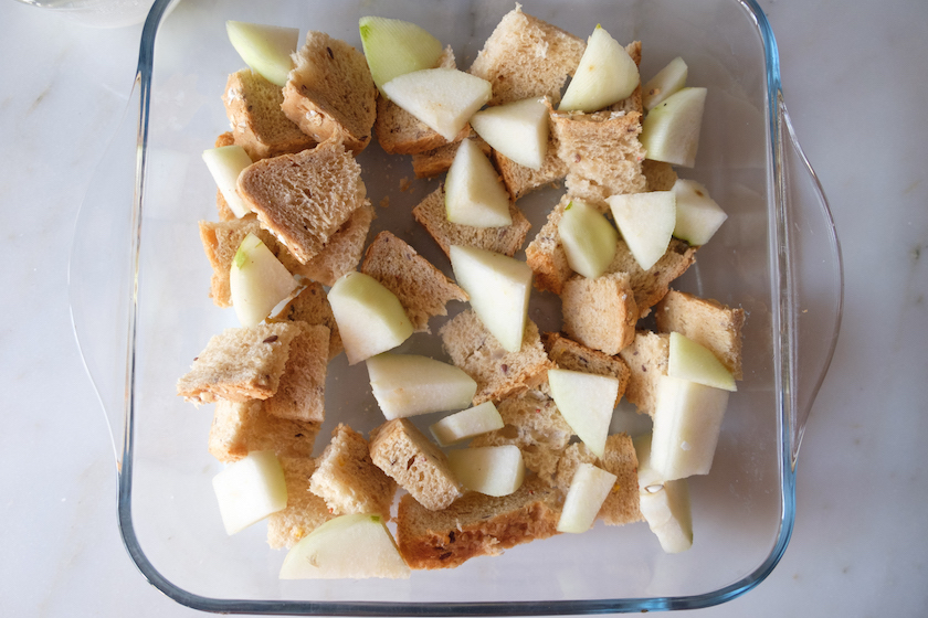 cubed breads and diced pears are taken in a glass baking tray