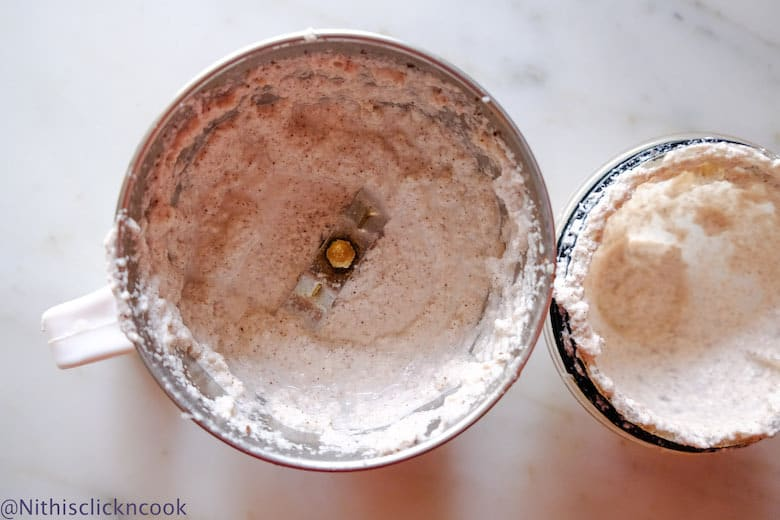 Finely ground coconut mixture in a blender with lid aside.