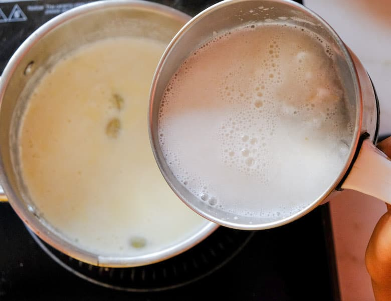 Tender coconut pulp in blender is being added to hot boiling milk
