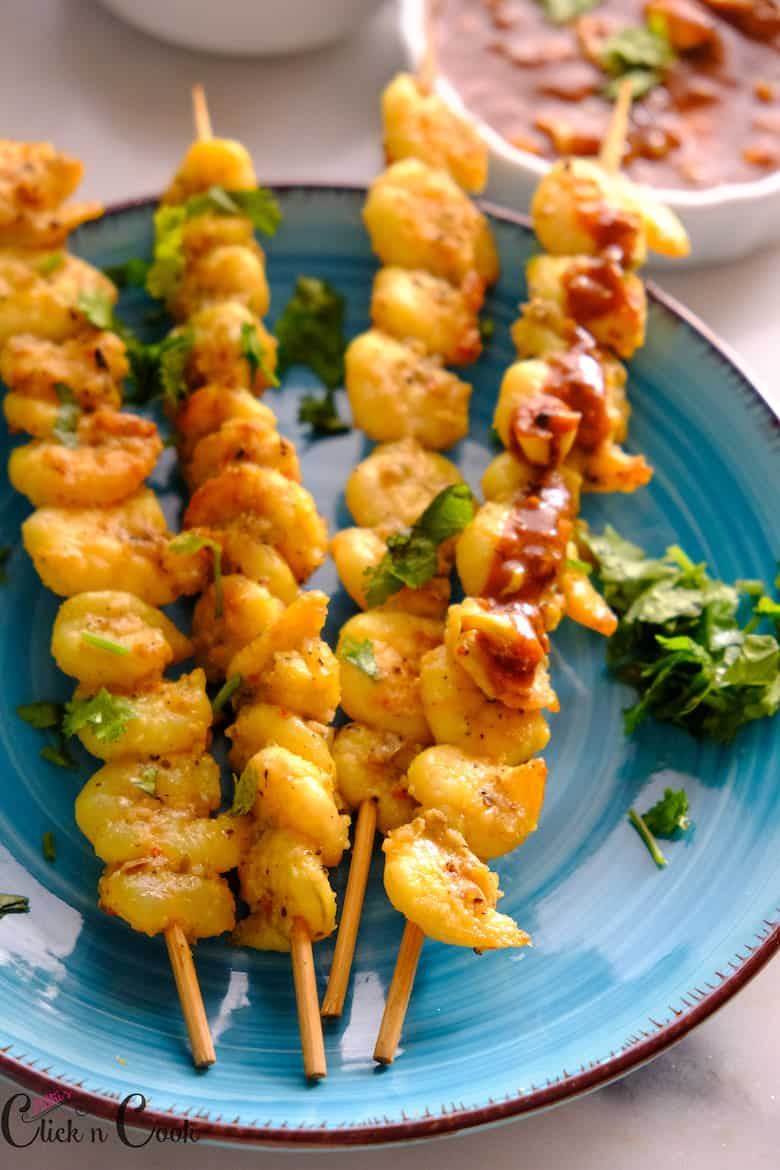 Skewered garlic shrimp smothered with tomato garlic dip served in plate. sprinkled with coriender leaves