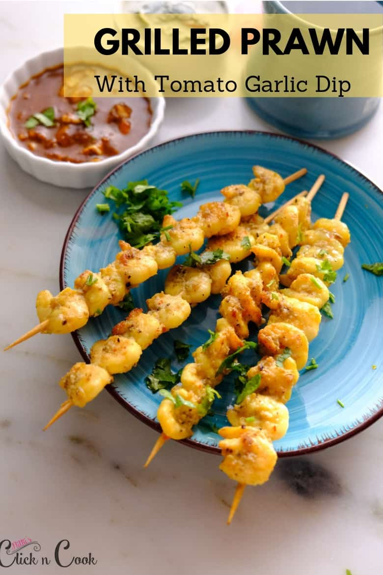 Skewered shrimp sprinkled with chopped coriender leaves served in blue plate with tomato dip aside.