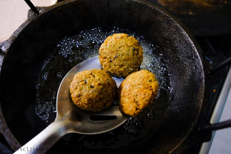 deep fried falafel is being drained out the oil using ladle