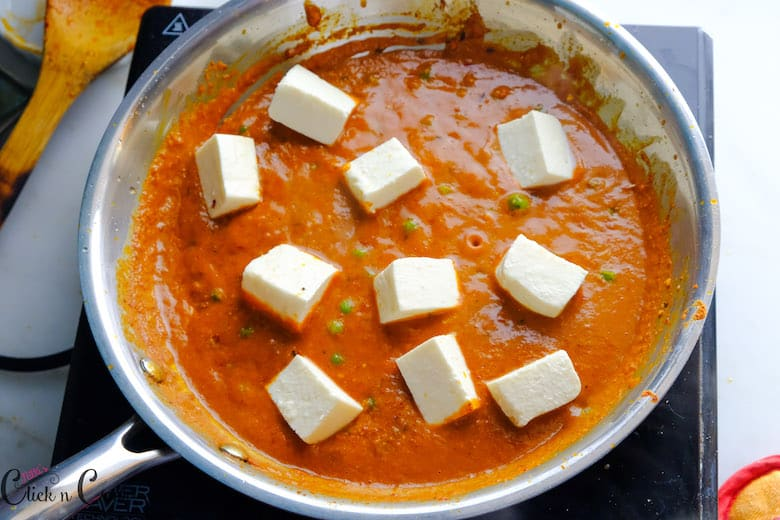cottage cheese is being added to gravy in suate pan