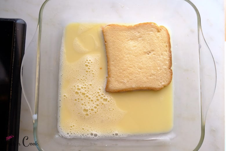 bread is soaked in egg milk mixture in glass tray