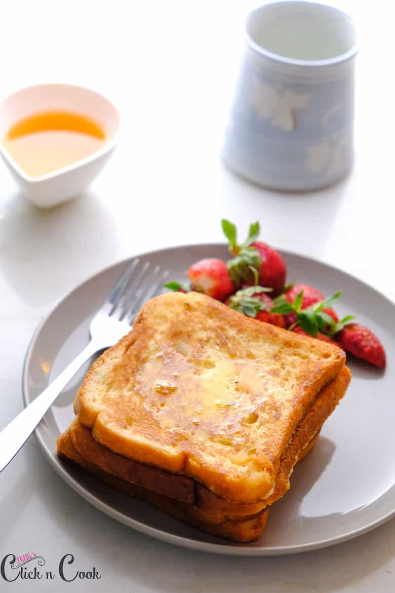 Classic French Toast is drizzled with maple syrup served in a small serving plate with fork, strawberries and maple syrup aside.