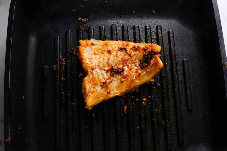 fish is being grilled