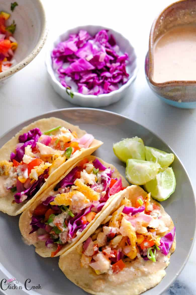 Fish tacos is served in grey ceramic plate with sliced lemon and taco sauce aside