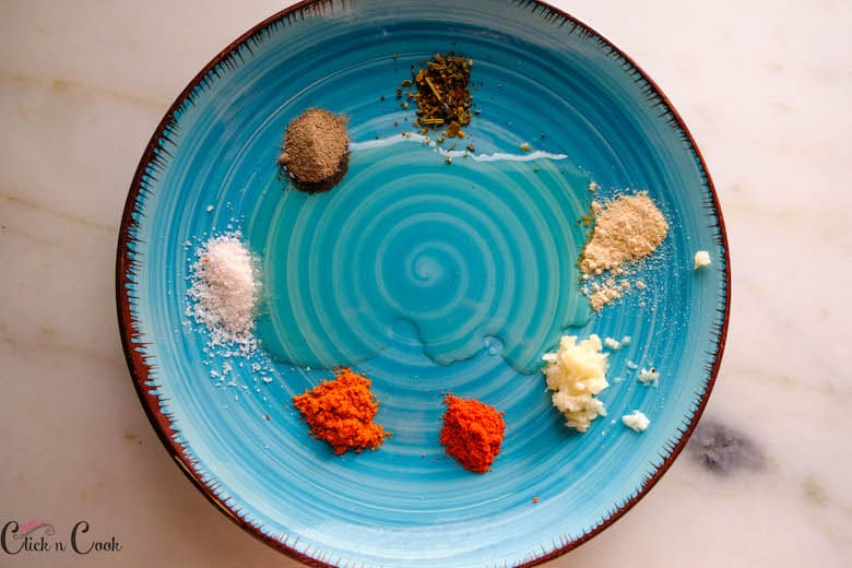 olive oil is being added to spices on plate