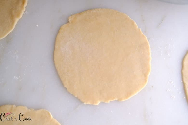 Tortillas are rolled to thin disc on marble working surface