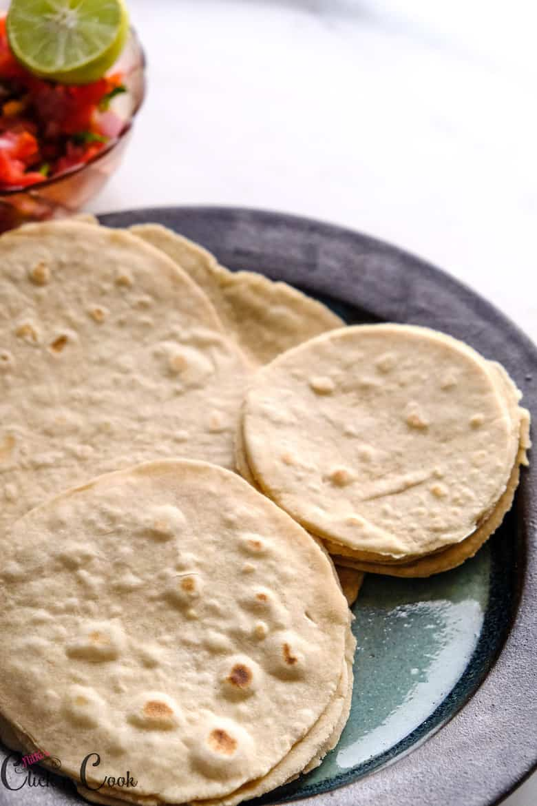 close up shot of tortillas served in plate with salsa aside