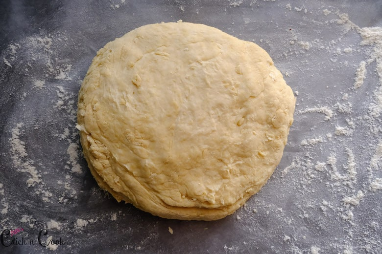 Soda bread dough is being rolled to bring a round shape on dusted baking sheet