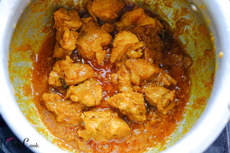 Mutton is being cooked with spices in deep pot