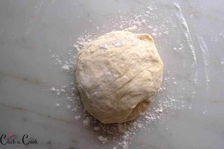 the best homemade Pizza dough is being rolled to make a round ball shape