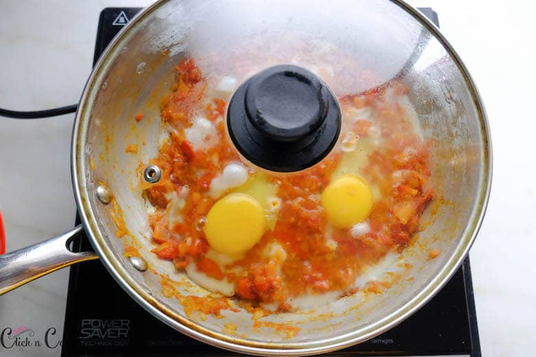 shakshuka is being cooked and covered with lid