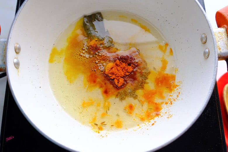 chili powder and turmeric powder is being added to oil in pan