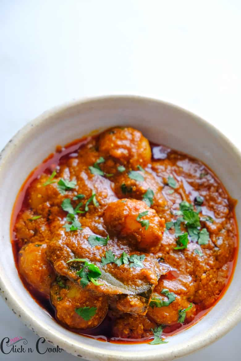 kashmiri dum aloo recipe is served in ceramic bowl, chopped coriender leaves are sprinkled on top