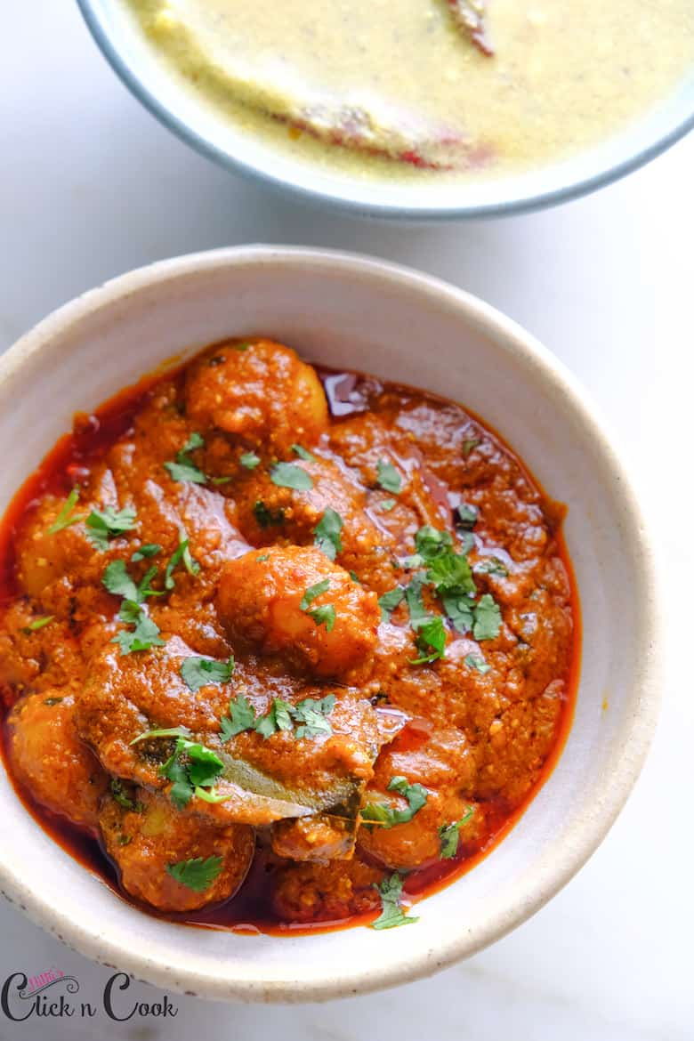 dum aloo sprinkled with chopped coriender leaves on top is served in beige ceramic bowl