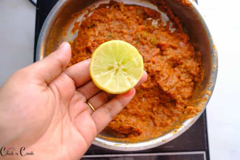 slice of lemon is being squeezed to pav bhaji