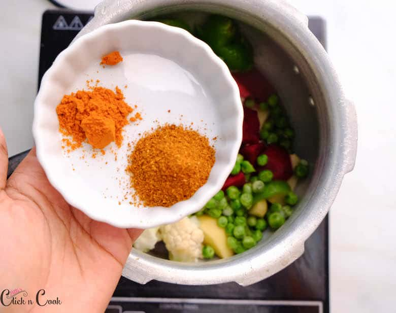 a bowl of spices is being added to the veggies in deep pot
