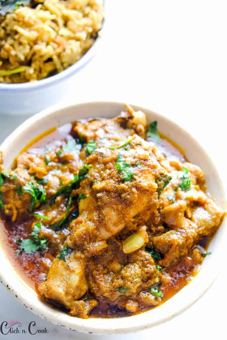 pepper chicken masala is served in bowl with bowl of rice aside