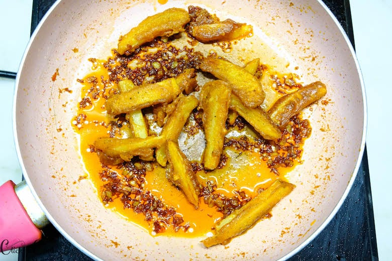 fried potato are being added to sauce