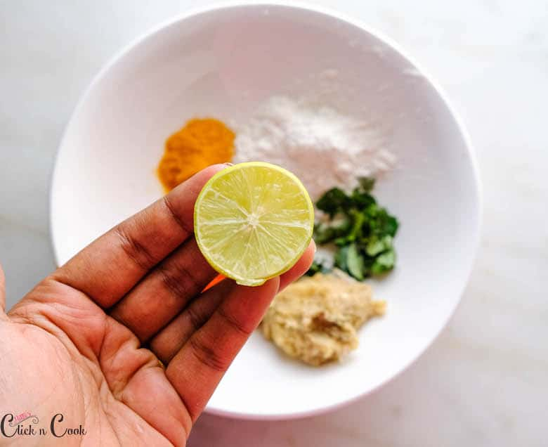 sliced half lemon is being squeezed to the bowl of spices