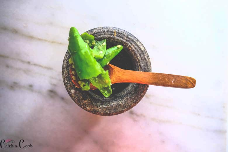 green chilli is being crushed in pestle mortar