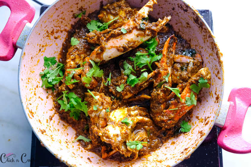 chettinad crab masala is being cooked, garnished with coriander leaves