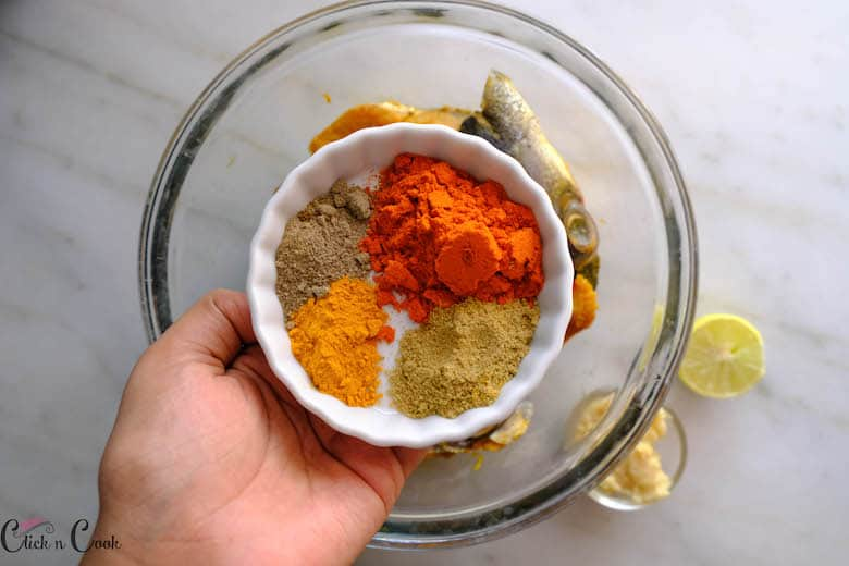 a bowl of spice powders is being added to fish
