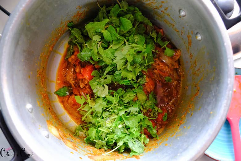 coriendar and mint leaves are added to the deep pot