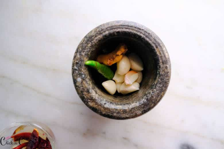 garlic and green chillies are in pestle mortar