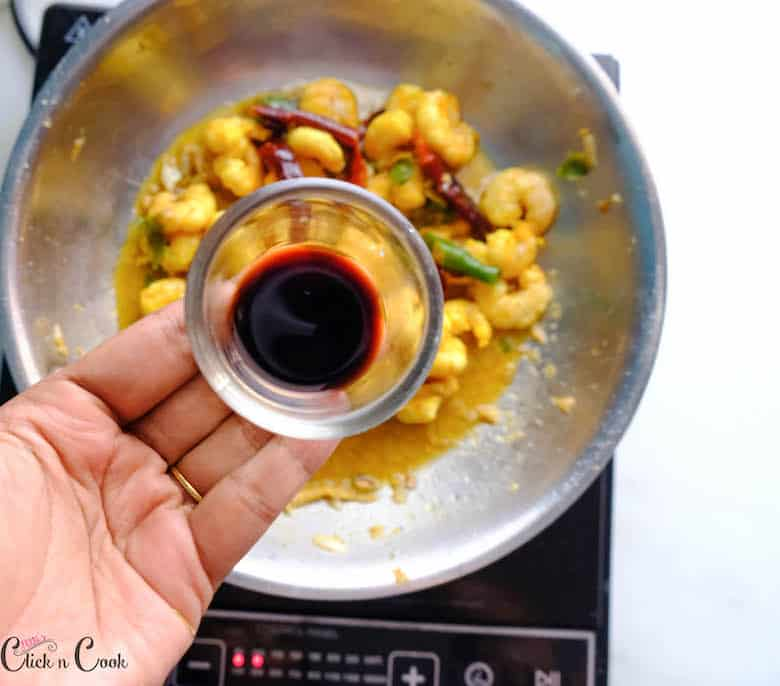 a bowl of soy sauce is being added to prawn/shrimp in wide saute pan