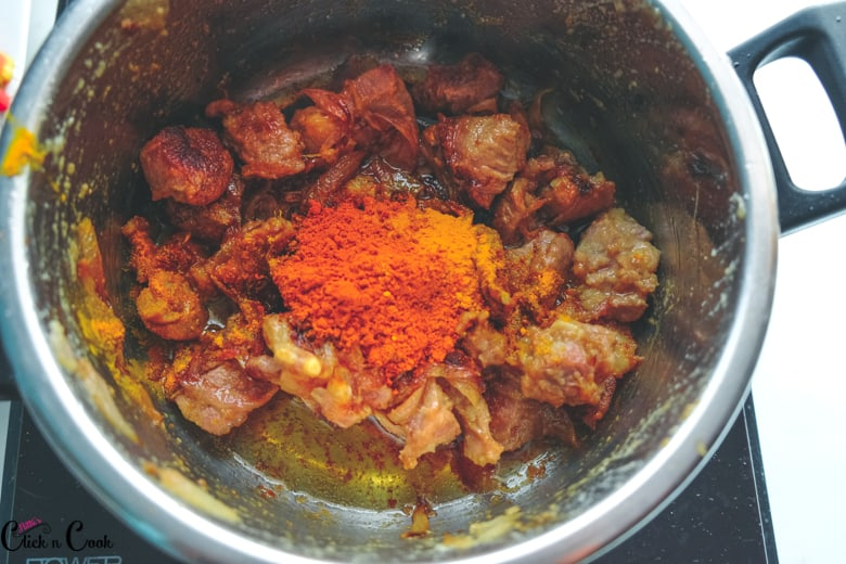 spice powders are added to mutton pieces in deep pot