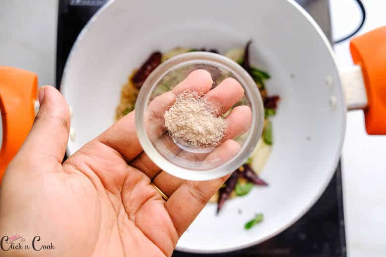 a small glass bowl of hing is added to the frying pan